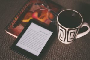 a kindle next to a cup of coffee