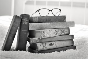 A pair of glasses on top of a pile of books